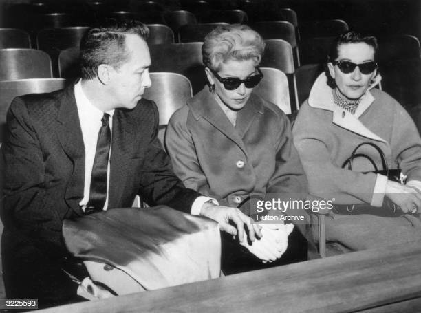 American actor Lana Turner wearing dark sunglasses sits next to her exhusband Stephen Crane in a courtroom during the murder trial of their daughter...