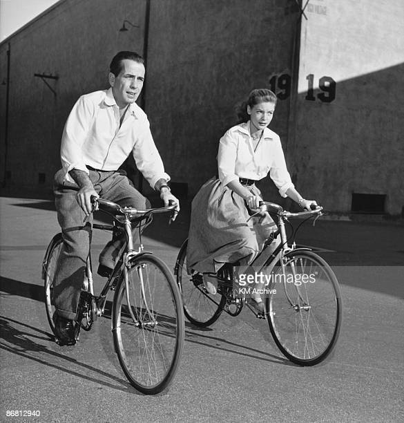 American actor Lauren Bacall and her husband actor Humphrey Bogart ride bicycles while on the set of the film 'Key Largo' Hollywood California 1948