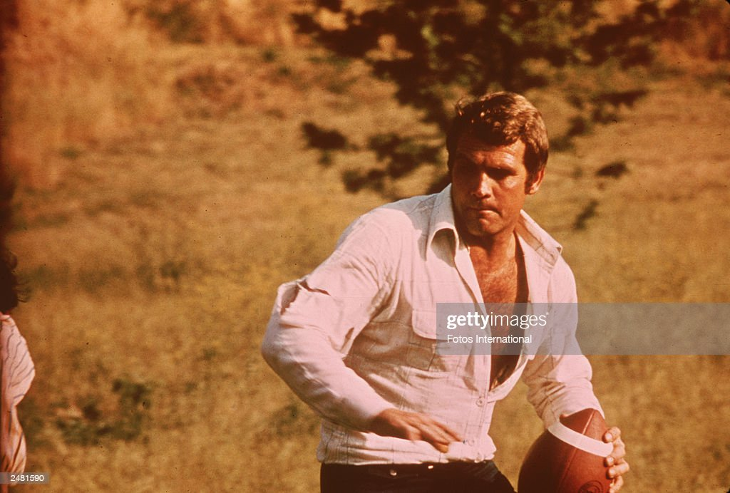 American actor Lee Majors holds a football in a still from the television series, 'The Six Million Dollar Man,' circa 1976.