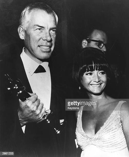 American actor Lee Marvin with Michelle Triola holding the Academy Award Oscar for best actor which he won for the film 'Cat Ballou' Original...