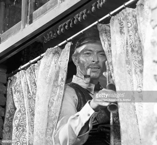 American actor Lee Van Cleef standing at the window holding a telescope in a scene from the film 'For a Few Dollars More' directed by Sergio Leone...