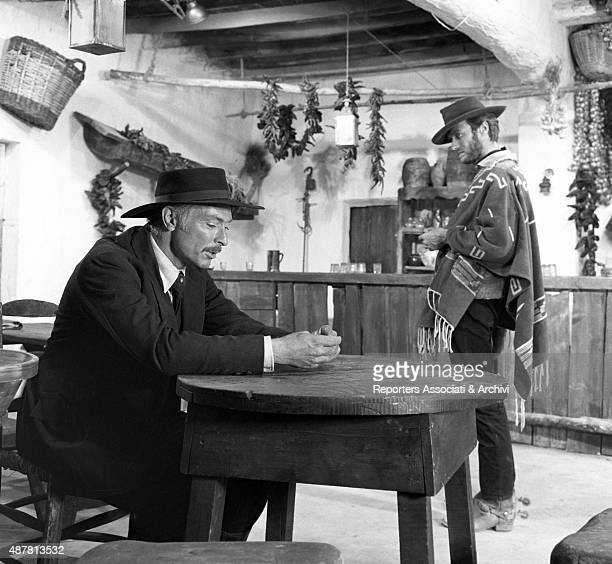 American actor Lee Van Cleef with American actor Clint Eastwood in the movie For a Few Dollars More directed by Sergio Leone The former is sitting at...