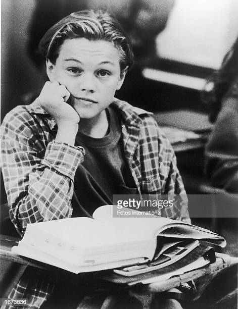 American actor Leonardo DiCaprio sits at a school desk with an open book in a promotional still from the television series 'Growing Pains' c 1991