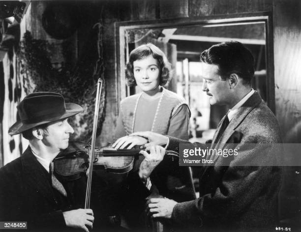 American actor Lew Ayres holds the hand of American actor Jane Wyman and places it upon a musician's fiddle in a still from director Jean Negulesco's...