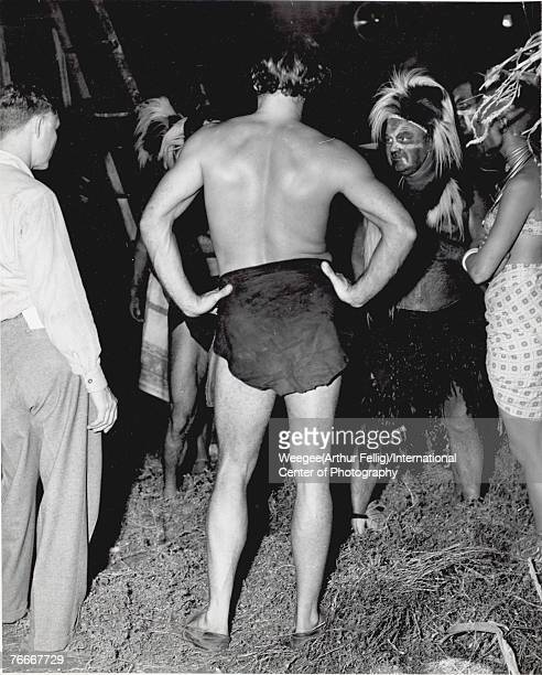 American actor Lex Barker stands with his hands on his hips in his Tarzan loincloth during a break in filming, late 1940s or early 1950s. Barker...