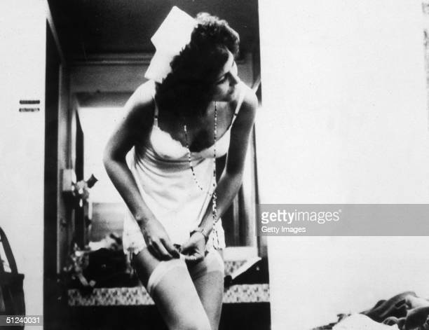 1972 American actor Linda Lovelace as Herself adjusts her garter in a still from director Gerard Damiano pornographic film 'Deep Throat'