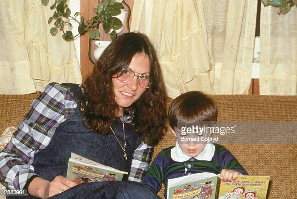 American actor Linda Lovelace of 'Deep Throat' reads a book with her son 1986