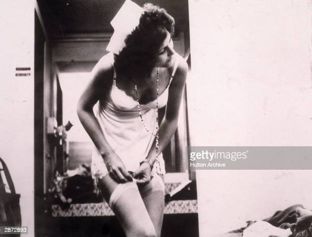 American actor Linda Lovelace removes her stocking, wearing a slip and a nurse's hat in a still from the film, 'Deep Throat,' directed by Gerard...