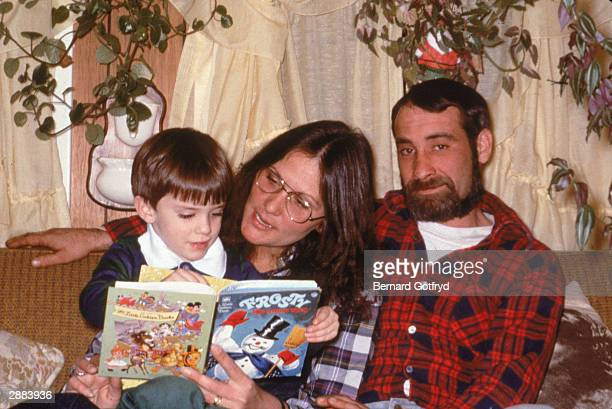 American actor Linda Lovelace , star of 'Deep Throat' reads to her son with her husband, Larry, 1986.