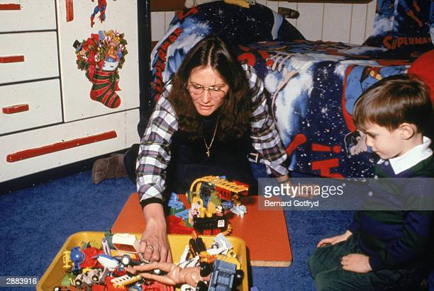 American actor Linda Lovelace star of the film 'Deep Throat' plays with her son circa 1980s