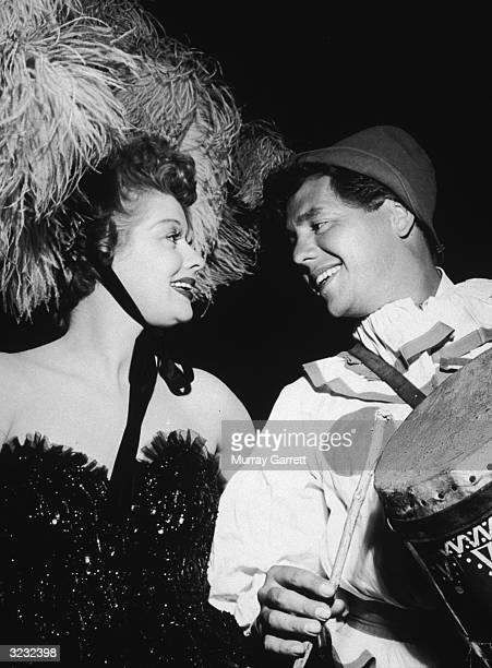 American actor Lucille Ball and her husband, Cuban-born actor and musician Desi Arnaz , both in costume, smile at each other backstage at a circus...