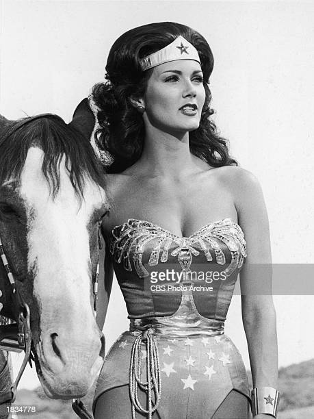 American actor Lynda Carter stands next to a horse in a still from the television series 'Wonder Woman' 1978