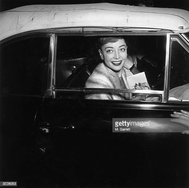American actor Marie Windsor smiles from an automobile window as she arrives at the premiere of director John Huston's film 'Moulin Rouge' She holds...