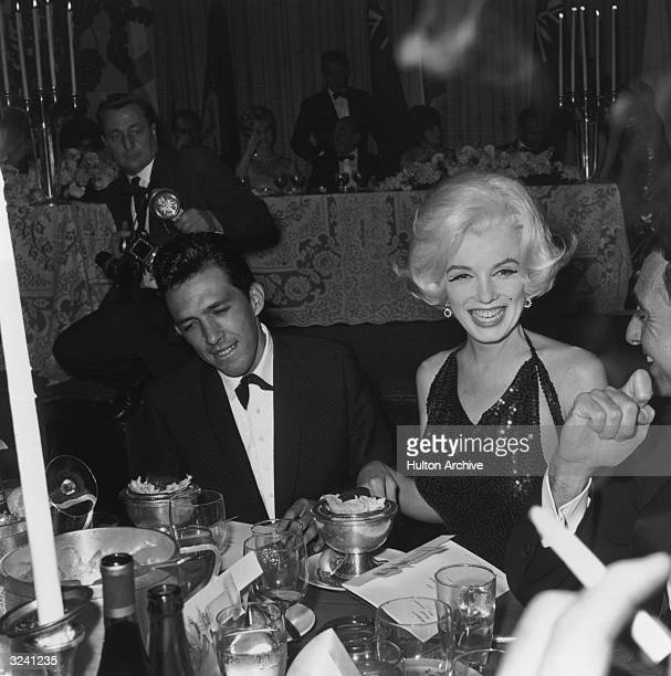 American actor Marilyn Monroe and her date writer Jose Bolanos sit at a dining table during the Hollywood Foreign Press Association Awards dinner...