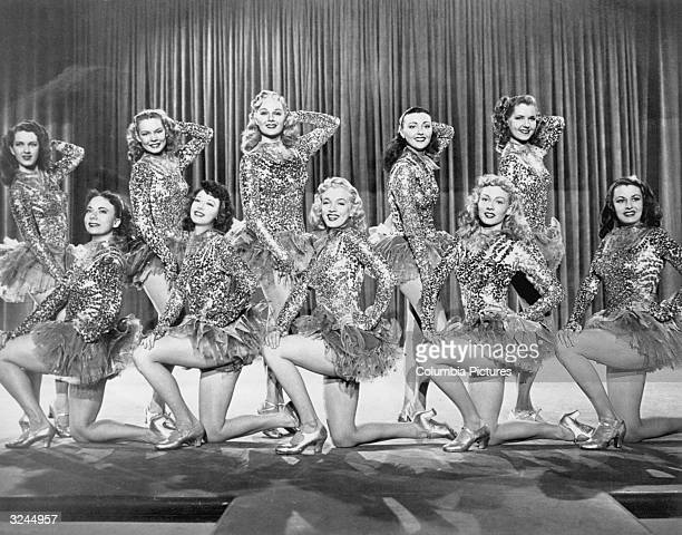 American actor Marilyn Monroe front row center posing on one knee in a chorus line of women wearing sequined costumes with tutus in a still from...