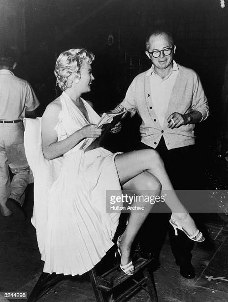 American actor Marilyn Monroe holds a script while sitting next to Austrianborn director Billy Wilder on the set of his film 'The Seven Year Itch'...