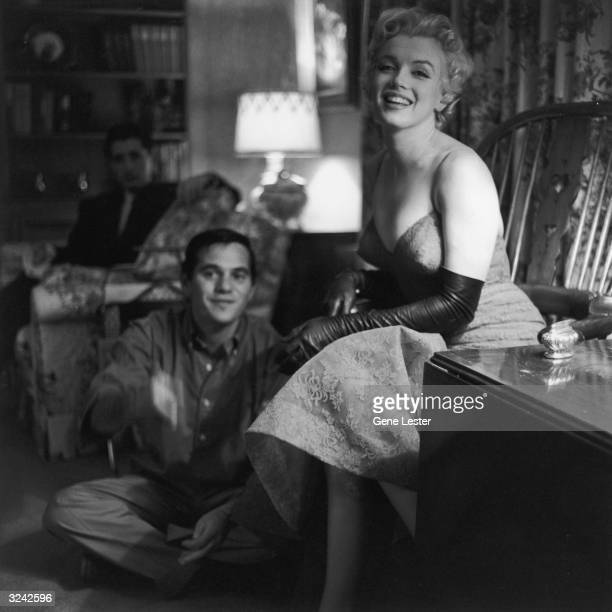 American actor Marilyn Monroe laughs while sitting next to photographer Milton Greene in a living room