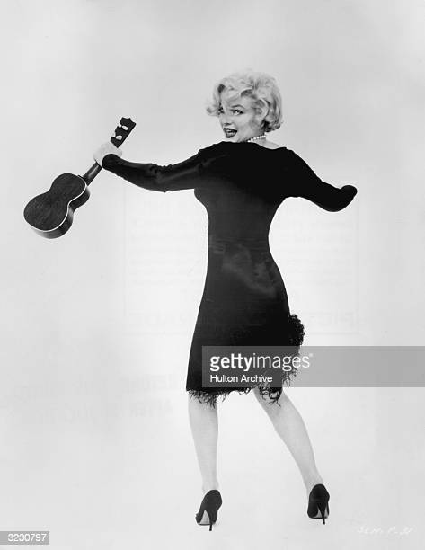 American actor Marilyn Monroe looks over her shoulder and shimmies while holding a ukulele in a promotional portrait for director Billy Wilder's film...