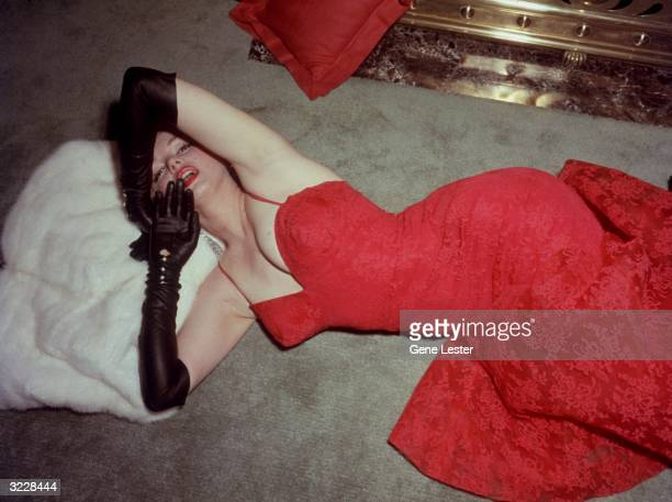 American actor Marilyn Monroe resting her head on a white fur coat while lying on a carpet in a red brocade evening gown and long black gloves