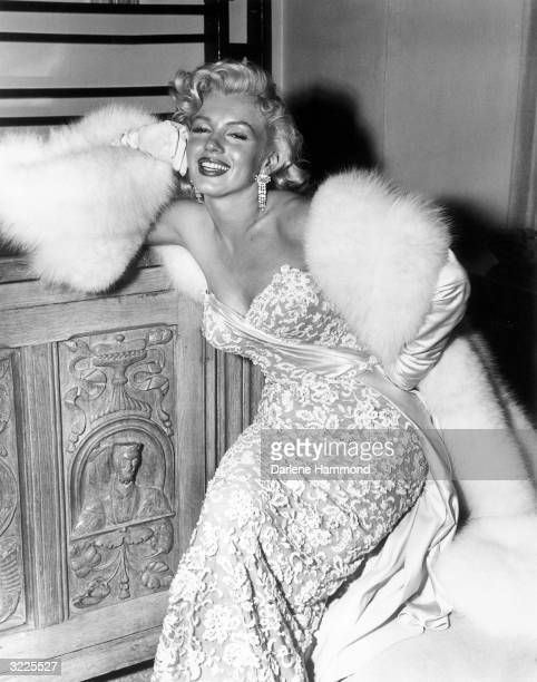 American actor Marilyn Monroe smiling as she sits at the home of director Jean Negulesco after the premiere of his film 'How to Marry a Millionaire'...