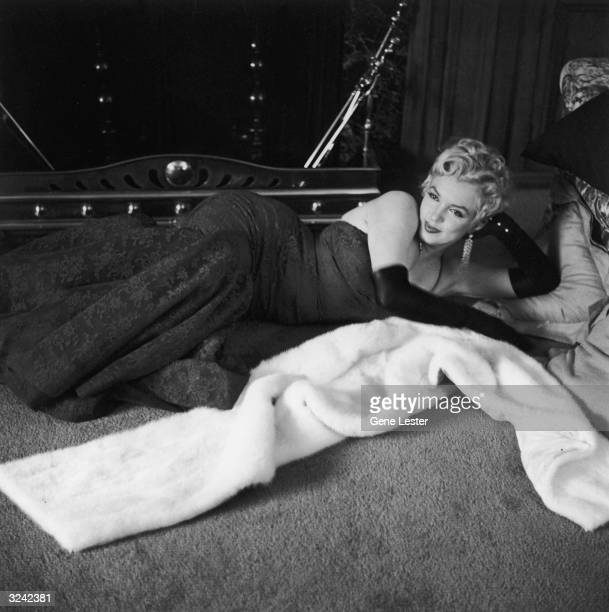 American actor Marilyn Monroe wearing a lace evening dress and long gloves lies in front of a fireplace next to her fur wrap
