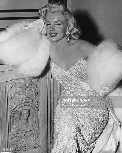 American actor Marilyn Monroe wearing white fur wrap and strapless evening gown leans on a wooden cabinet during a party for the film 'How To Marry A...