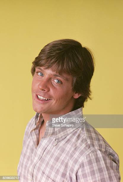 American actor Mark Hamill wearing a check shirt in a studio portrait against a yellow background circa 1975