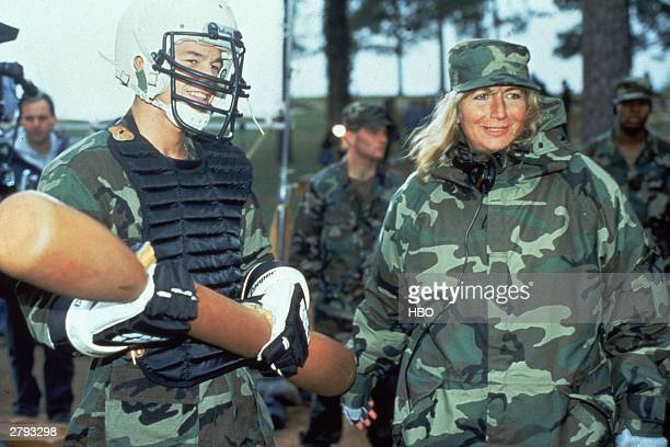 American actor Mark Wahlberg holding a bat and wearing military fatigues and a football helmet and American director Penny Marshall also in fatigues...