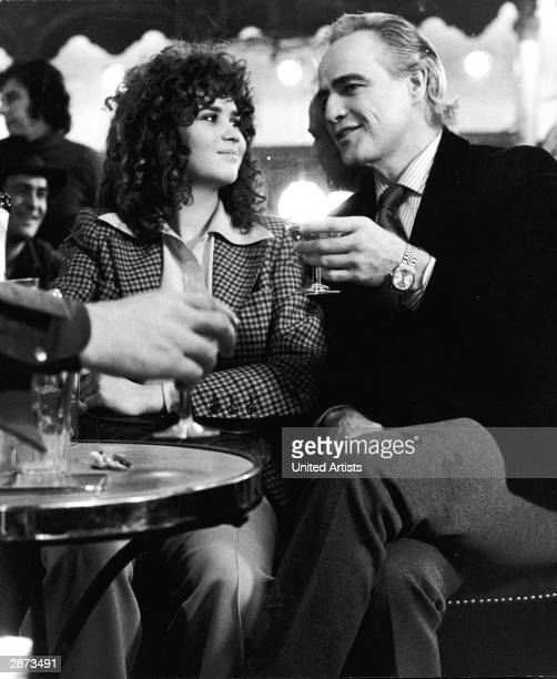 American actor Marlon Brando and French actor Maria Schneider drink in a bar in a still from the film 'Last Tango In Paris' directed by Bernardo...