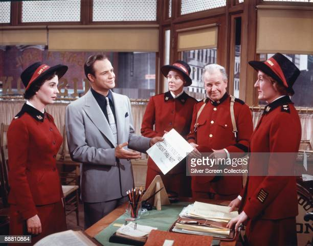 American actor Marlon Brando as Sky Masterson Jean Simmons as Sergeant Sarah Brown and Regis Toomey as Uncle Arvide Abernathy in the musical film...