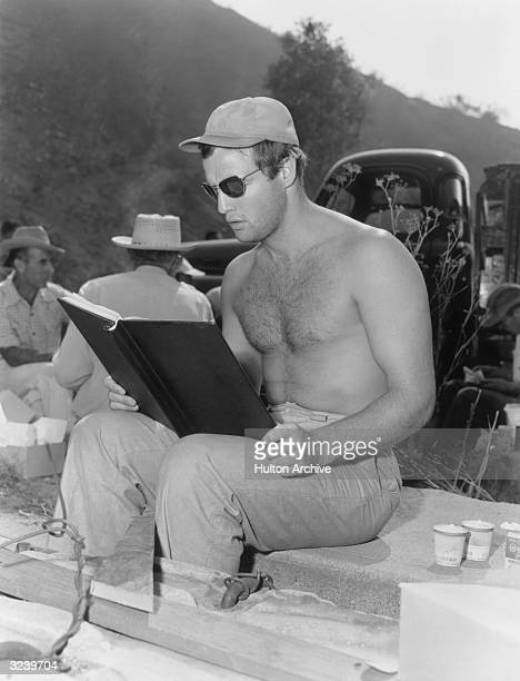 American actor Marlon Brando barechested seated on a block of cement and reading from a book on the outdoor set of the movie by director Joseph L...