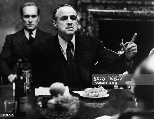 American actor Marlon Brando gestures at a table while American actor Robert Duvall sits behind him in a still from the film 'The Godfather' directed...