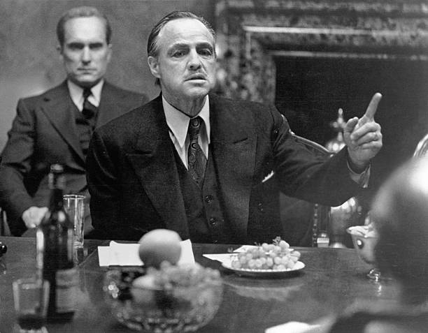American actor Marlon Brando , in character as mob kingpin Don Vito Corleone, gestures as he sits at a table as colleague and compatriot Robert...