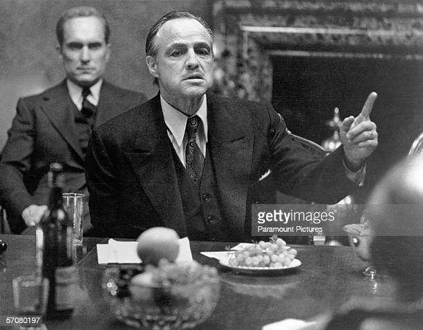 American actor Marlon Brando in character as mob kingpin Don Vito Corleone gestures as he sits at a table as colleague and compatriot Robert Duvall...
