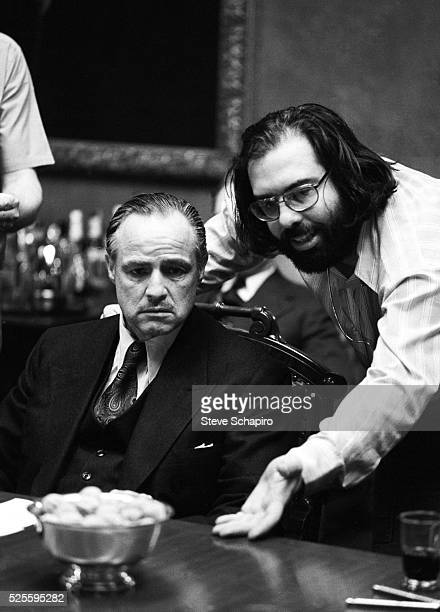 American actor Marlon Brando in costume as Vito Corleone receives instruction from American director and screenwriter Francis Ford Coppola during...