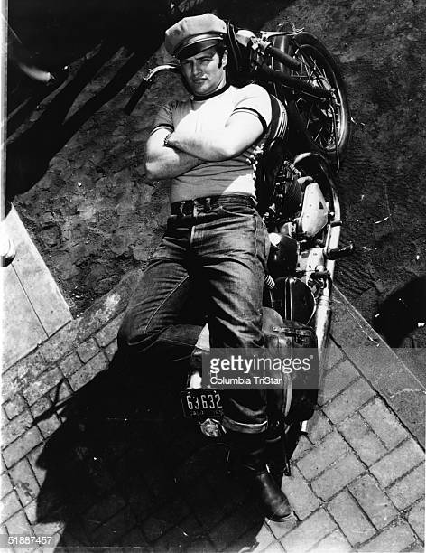 American actor Marlon Brando lies on a motorcycle in a publicity shot for the film 'The Wild One,' directed by Laszlo Benedek, California, 1953.