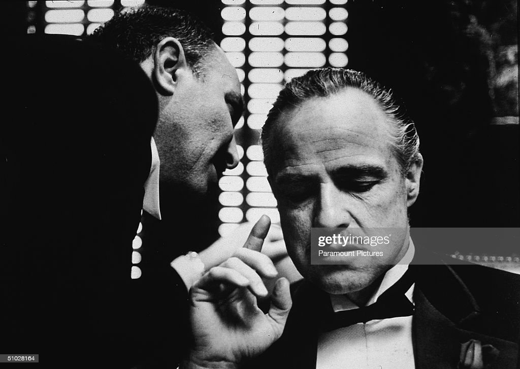 American actor Marlon Brando (1924 - 2004) listens as an unidentified actor speaks close to one ear in a still from the film, 'The Godfather,' directed by Francis Coppola, 1972.