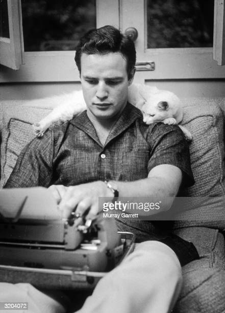 American actor Marlon Brando sits on a sofa with a typewriter in his lap while a cat lays across his shoulders at his home in Los Angeles California