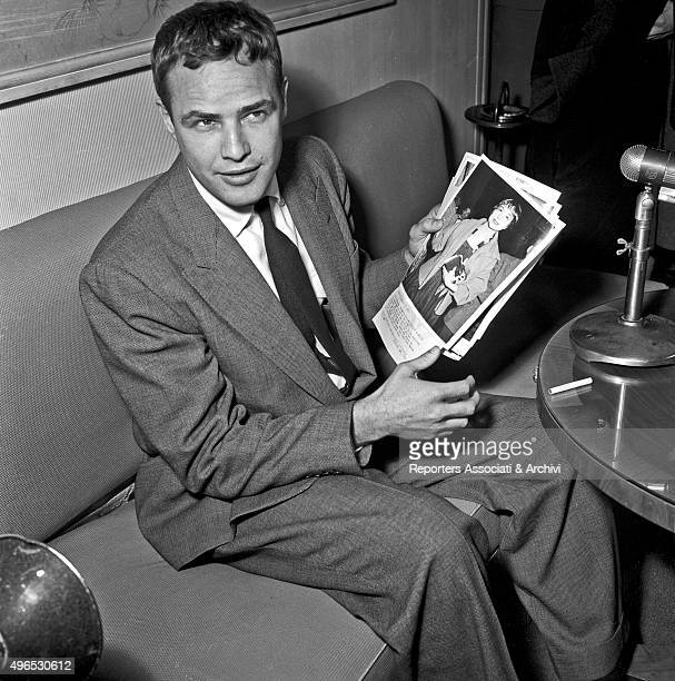 American actor Marlon Brando sitting on a sofa showing a photograph during a press conference Rome 1956