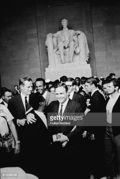 American actor Marlon Brando stands with his arm around poet James Baldwin surrounded by actors Charlton Heston Harry Belafonte and others gathered...