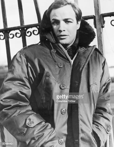 American actor Marlon Brando wears a parka and leans against an iron fence on the set of the film 'On the Waterfront,' directed by Elia Kazan.