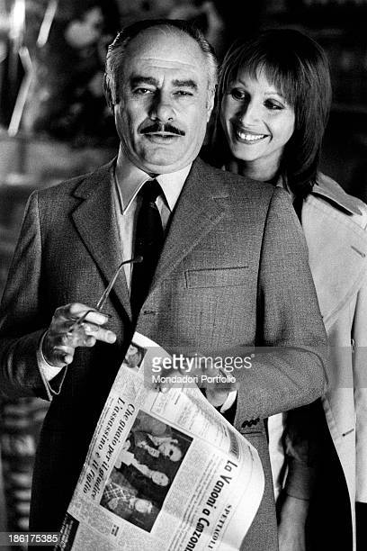 American actor Martin Balsam holding a newspaper with an article about Ornella Vanoni beside the smiling Italian actress Paola Pitagora They're on...