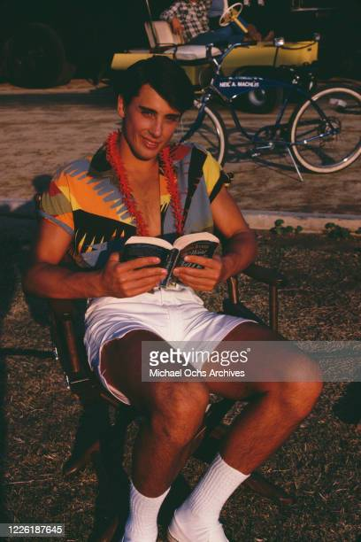 American actor Matt Lattanzi wearing a patterned shirt with white shorts reading a book on the set of 'Grease 2' in Norwalk California December 1981