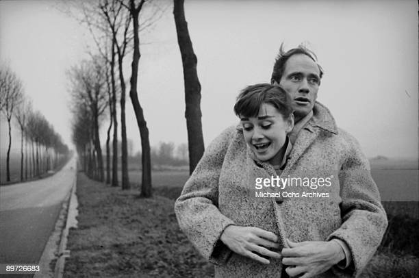 American actor Mel Ferrer buttons up his coat around his wife, actress Audrey Hepburn , on a country road outside Paris, 1956.