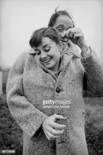 American actor Mel Ferrer buttons up his coat around his wife actress Audrey Hepburn on a country road outside Paris 1956