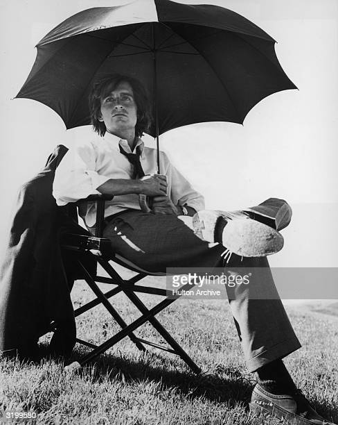 American actor Michael Douglas sits under an umbrella in a director's chair during a break in the production of director David Miller's film 'Hail...