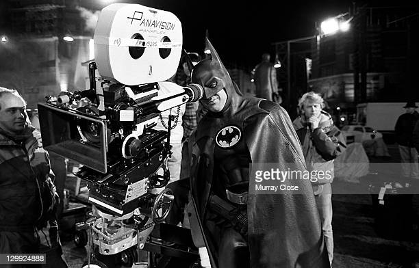 American actor Michael Keaton tries the view from behind the camera, during the filming of 'Batman', 1989.
