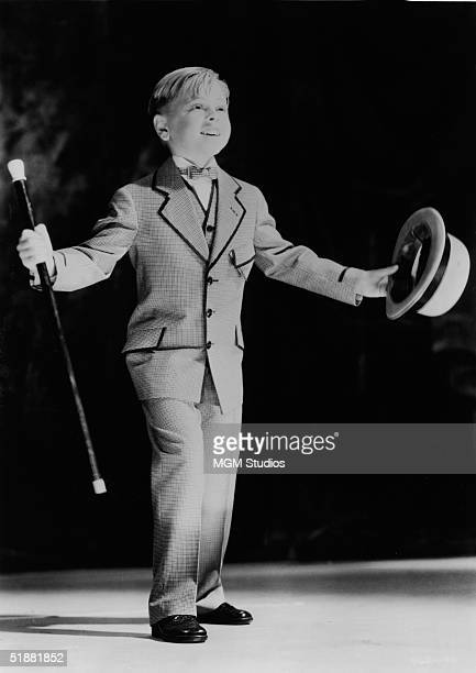 American actor Mickey Rooney dances on stage as he wears a suit which suggests the vaudeville music hall performers of a bygone era in a still from...
