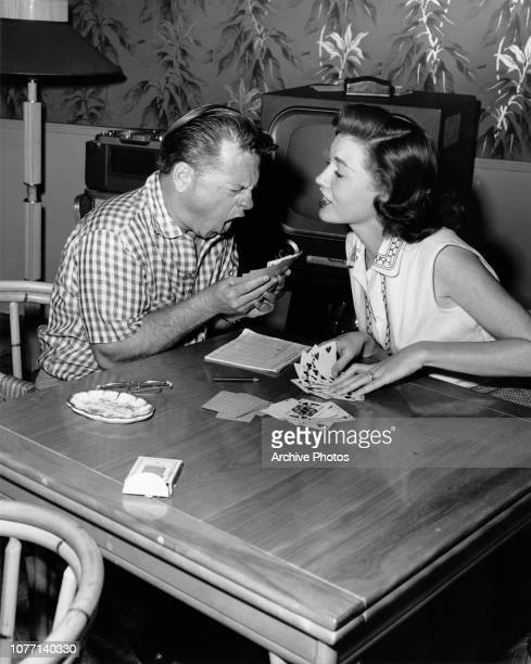 American actor Mickey Rooney loses a card game to his wife actress Elaine Devry circa 1955