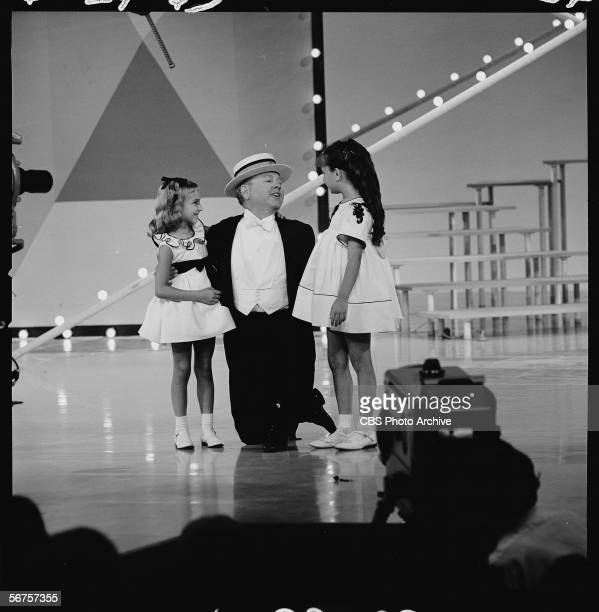 American actor Mickey Rooney performs on his knres with two unidentified girls during an episode of 'The Judy Garland Show' June 24 1963